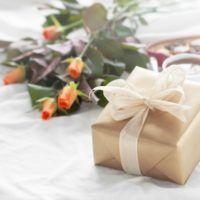 paquete-de-regalo-dorado-con-un-ramo-de-flores-y-bombones_1220-667